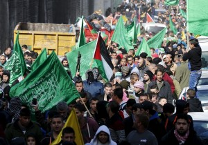 A Palestinian militant holds up a weapon as others wave Hamas flags during the funeral of Mohammed Ali in the East Jerusalem refugee camp of Shuafat, in an area Israel annexed to Jerusalem after capturing it in the 1967 Middle East war, January 5, 2016. Ali was shot dead by Israeli police on October 10, 2015, after he stabbed two Israeli police officers, seriously wounding one of them, near Damascus Gate, outside Jerusalem's Old City, Israeli police spokesman Micky Rosenfeld said. REUTERS/Ammar Awad  - GF10000283058